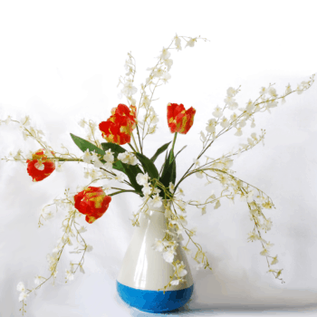 Tall red tulips combined with white dancing orchids in a Piet Hein Eek vase